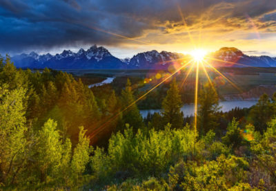 The setting sun briefly breaks through the thunderstorm clouds to illumnitate the spring aspens in Grand Teton National Park