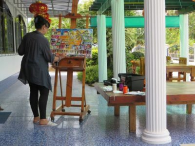 Artist working on our terrace on the banks of the Mekong River in NE Thailand