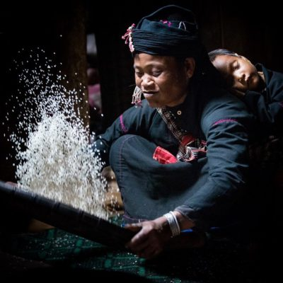 Luminous Journeys photo tours with En tribe tossing rice with baby on her back