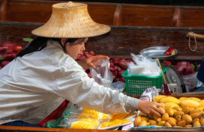 Merchant selecting fruit for a customer at the Damnoen Saduak Floating Market. Floating markets were common at one time in the history of Bangkok but today only a few remain. Bangkok was called Venice of the east at one point in its long history because of the many canals throughout the city. The Damnoen Saduak market is about 62 miles outside of Bangkok and is the best known and most visited of floating markets today.